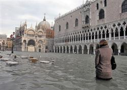 Mulher caminha pela alagada Piazza San Marco